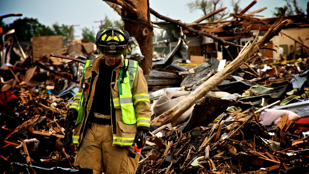 A firefighter looks for remains following the Joplin Tornado